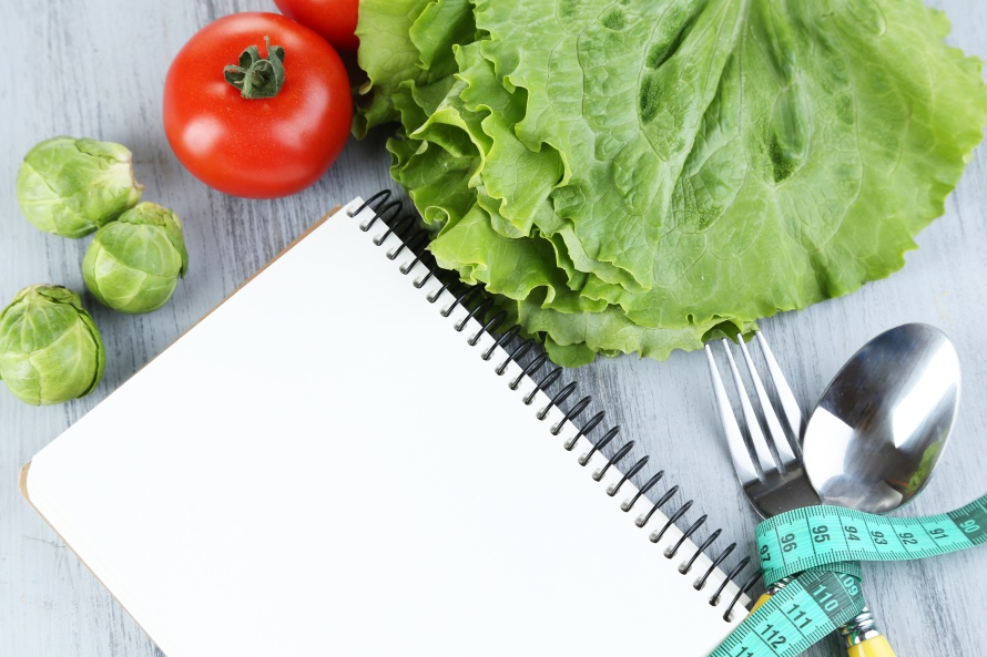 Cutlery tied with measuring tape and notebook with vegetables