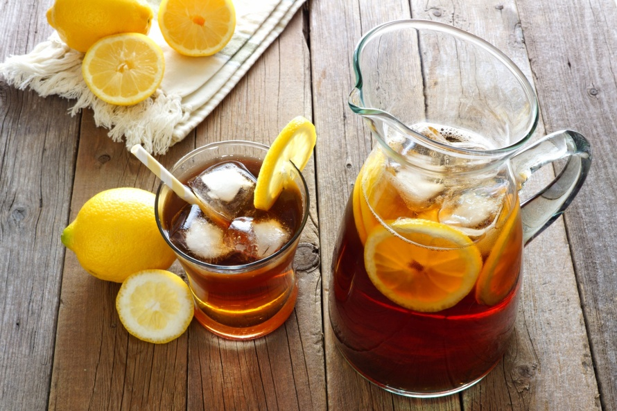 Pitcher of fresh lemon iced tea with filled glass on a rustic wooden background