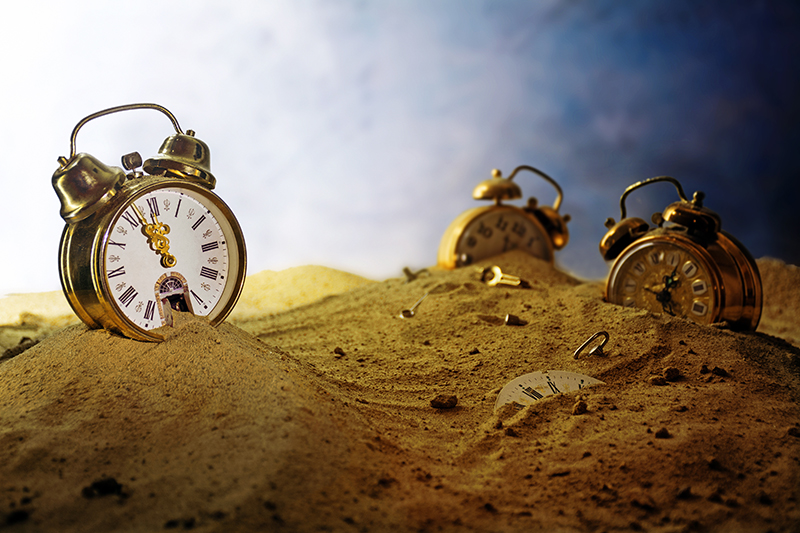 sand running out of an alarm clock, other watches sink into it,