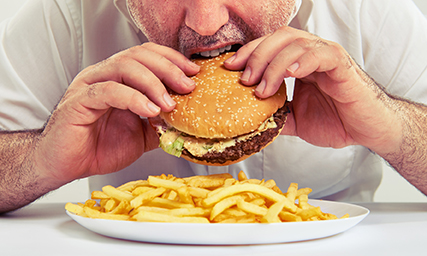 man eating burger and french fries