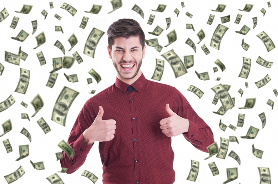 Excited businessman raising thumbs up and standing under money r