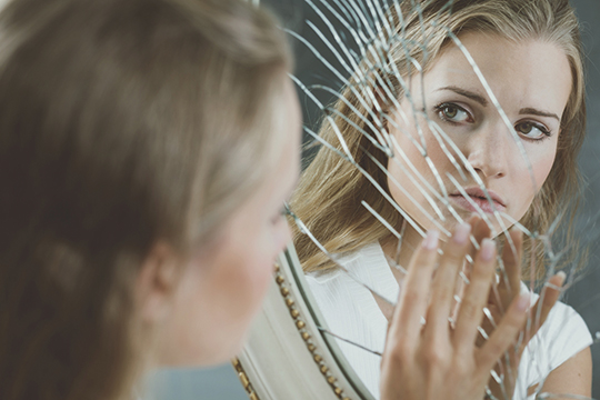 Woman touching broken mirror