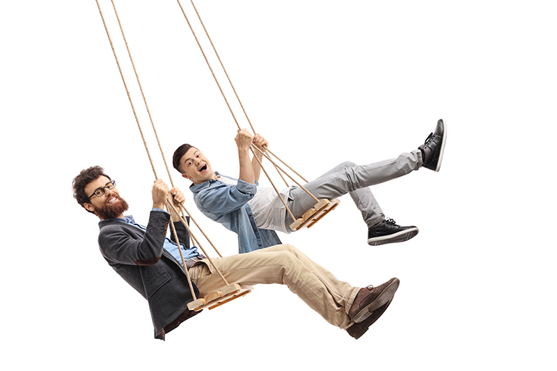 Joyful father and son swinging on wooden swings