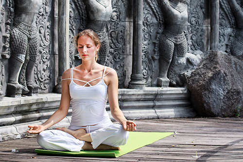 Young woman doing yoga in abandoned temple on wooden platform. Practicing.