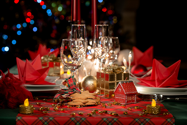 red and golden christmas table decoration with dim light candle