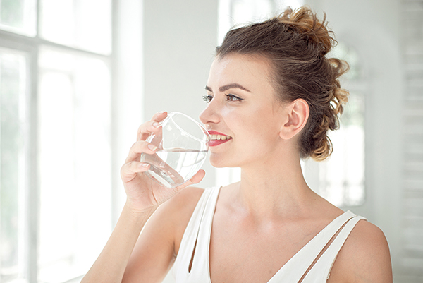 Portrait of a beautiful woman drinking water