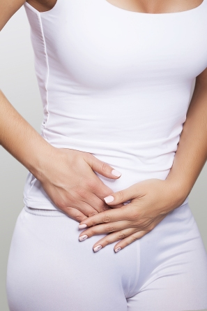 Stomach ache. Painful sensations on the right side of the abdomen. Appendicitis. Young woman holding hands on her stomach. The concept of health. On a gray background.
