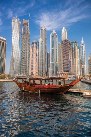 Dubai Marina with boats against skyscrapers in Dubai, United Ara
