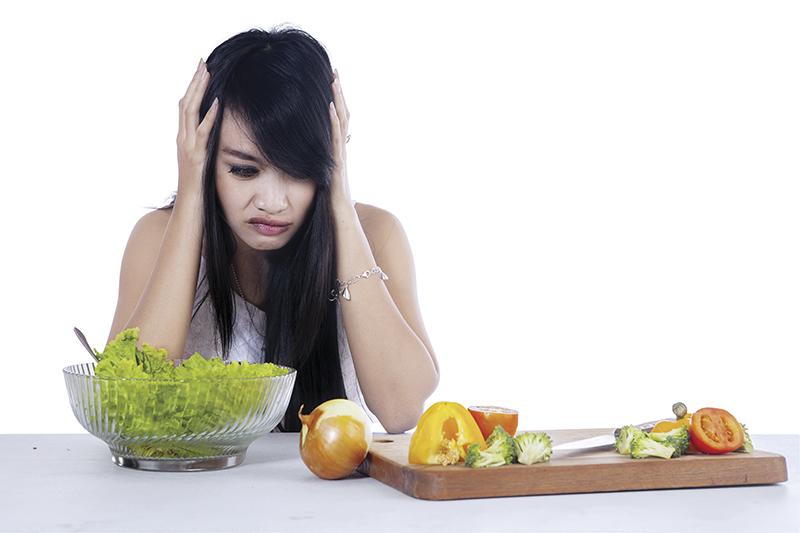 Woman hesitate to eat salad 1