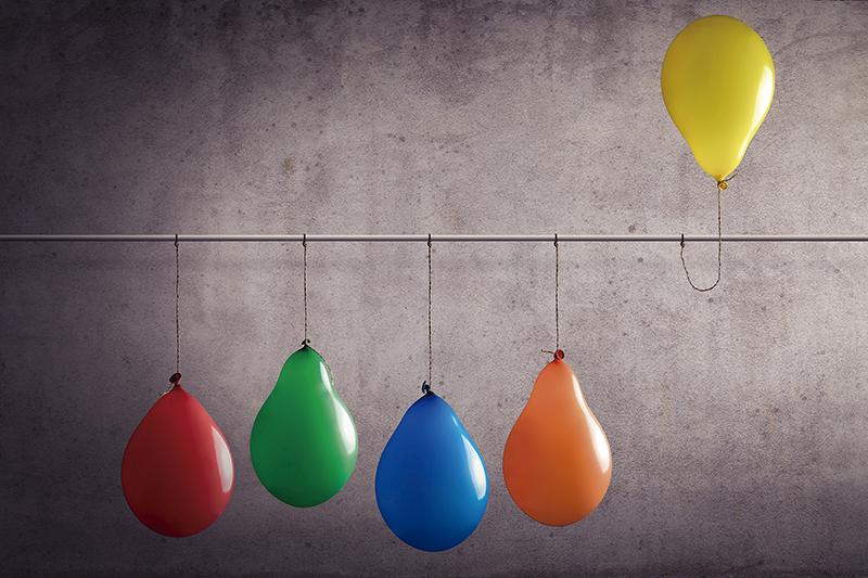 Ein Luftballon der aus einer Gruppe heraussticht