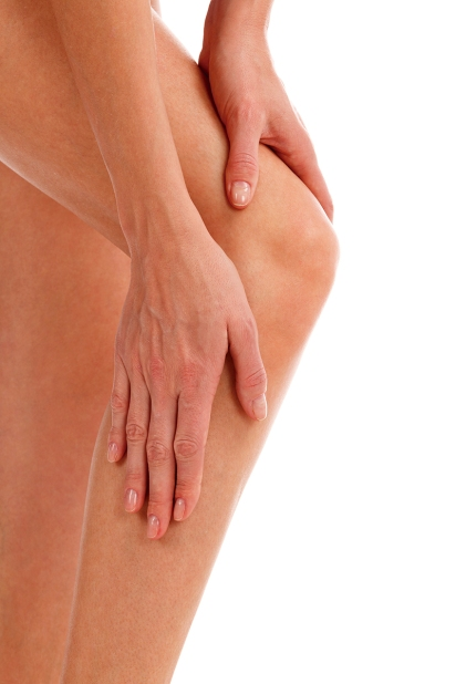 Closeup shot of woman holding sore knee, isolated on white backg
