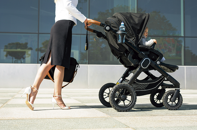 Business mother pushing baby on the way to work