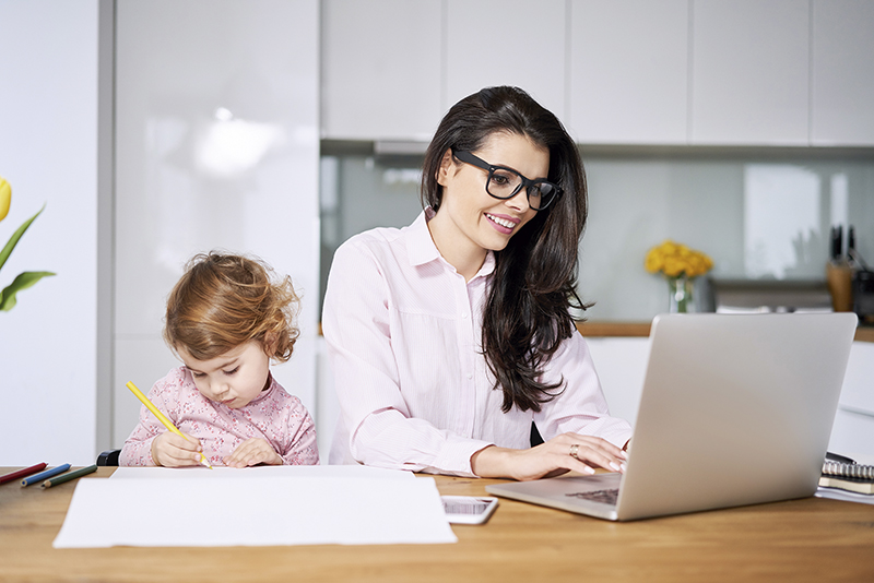 Working mother concept. Young woman working on laptop with her child from home