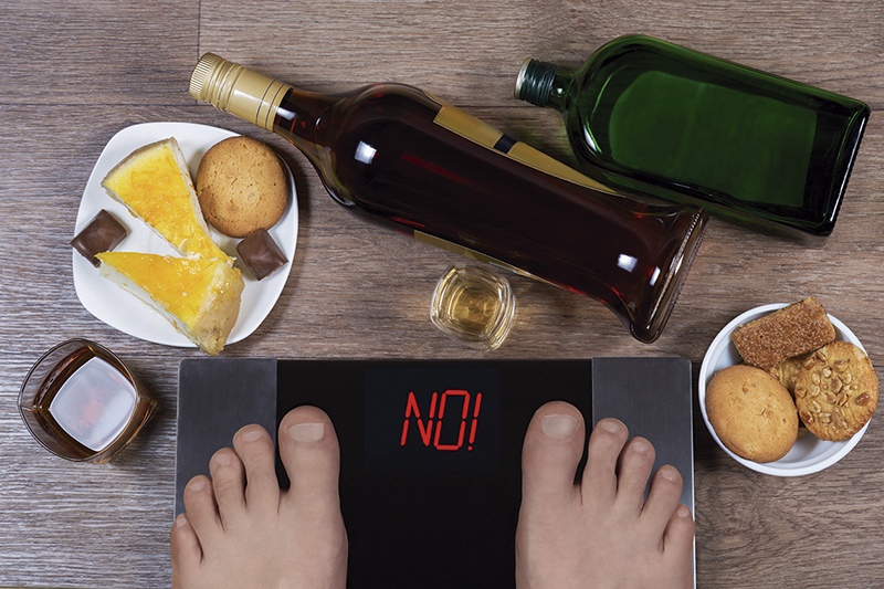Male feet on digital scales and sign no surrounded by bottles an