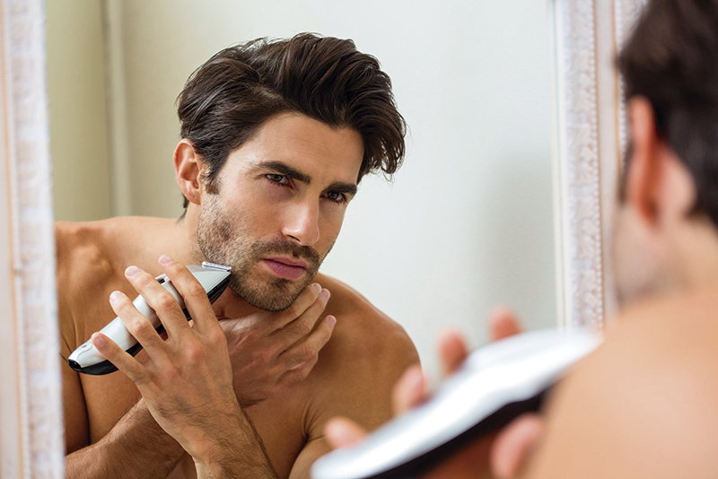 Young man shaving with trimmer